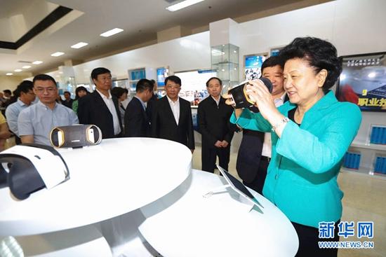 1中共中央政治局委员、国务院副总理刘延东在天津广播电视大学职业教育周体验区,通过全景VR设备体验汽车修理培训课程。.jpg
